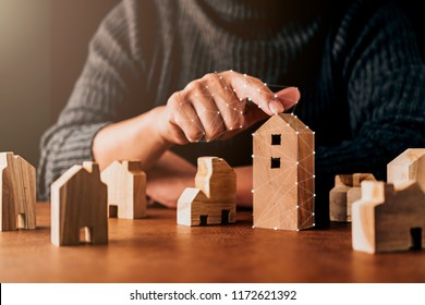 house design decision ideas concept with man hand pick house shape wooden model on brown table