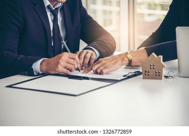 House developers and customers hand to sign in contract buy new house or Agree to make a home loan and buy home insurance with real estate agent showing a house .