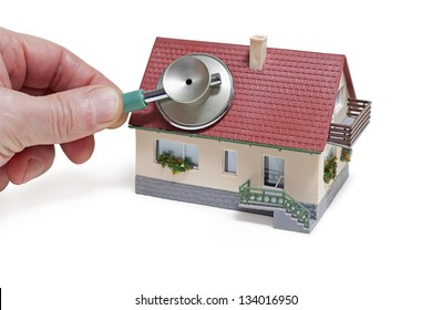 House diagnostics. Model house with hand and stethoscope on white background