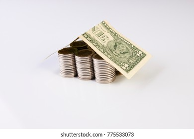 House from dollars costs on stacked coins