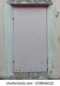 The house door is light pink, old condition, plastered white, with orange tone background