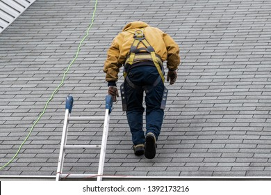House during day with gray color Single Family Home and construction man in yellow uniform walking on roof shingles and ladder during repair