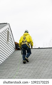 House during day with gray color home and construction man in yellow uniform walking on roof shingles and ladder during repair
