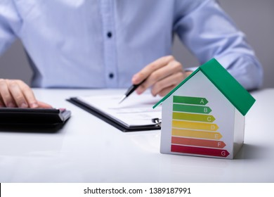 House With Energy Efficiency Rate In Front Of Businesspeople Working In Office While Using Calculator