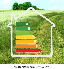House with energy efficiency scale image on green field background