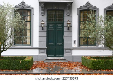 house entrance with green door and pavement with orange leafs
