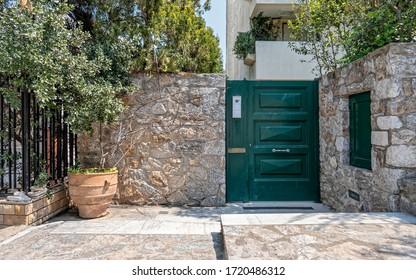 Hauseingang grün gestrichene Metalltür und Topfpflanze am Bürgersteig