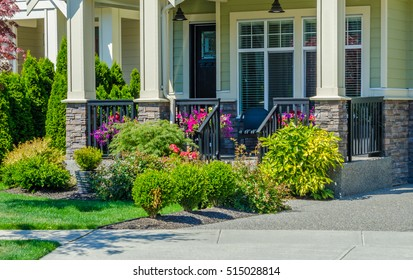 House entrance with nicely landscaped and trimmed front yard.