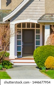 House entrance with nicely trimmed and landscaped front yard, lawn.