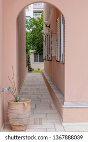 house entrance private alley with potted plant and dark pink walls, Athens Greece