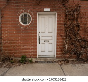 House entrance with white door and round window with vines on brick wall