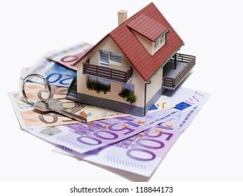 House with Euro banknotes and house key over white background