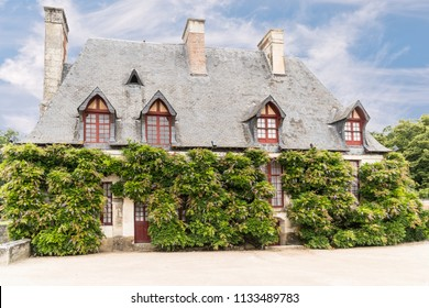 House in Europe with Red Door and Windows and Climbing Wisteria Growing and Covering Front of the House.