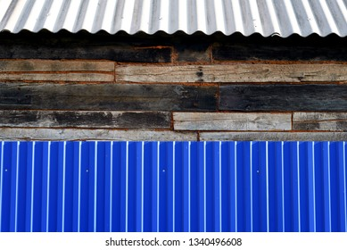 House exterior of a blue metal fence and old aged wooden walls with a grey asbestos style roof
