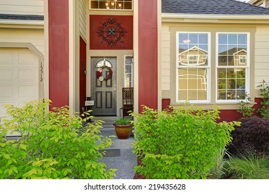 House exterior. Entrance porch with black door and red trim.