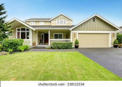 House exterior. Spacious walkout deck with railings. Garage with driveway