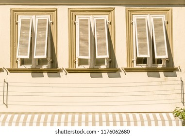 House facade with stucco 3 windows and unfolded wood shutters awning climbing aid