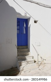 House facade white and blue colors in historic center of Ibiza, house of ibiza, Spain, indigo door, cobbled streets and steep, narrow streets and charming Mediterranean style, minimal iron railing,