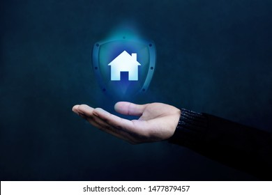 House or Family Insurance Concept. Company Supporting and Protecting their Customer by Shield, Home Icon floating over a Careful Gesture Hand of a Businessman