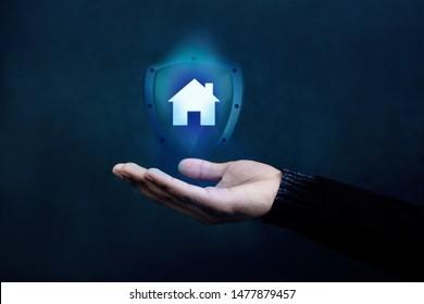 Haus- oder Familienversicherungskonzept. Unternehmen, das ihren Kunden durch Schild unterstützt und schützt, Home Icon, das über eine vorsichtige Hand eines Geschäftsmanns schwebt