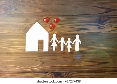 house, family of paper on a wooden background
