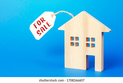 House figure and for sale price tag. Selling real estate, lower prices because of a falling market and reduced demand. Realtor Services. Investing in housing to save during an economic downturn.