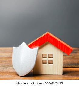 House figurine and protective shield. The concept of home security and safety. Alarm systems. The inviolability of private property, protection against raiders or unauthorized access.