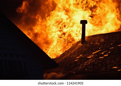 House fire with heavy flame, glowing roof and chimney.