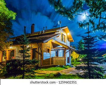 House. Flying clouds. The light of the moon at night. Cottage at night. Cottage village. The house is lit by the moon.