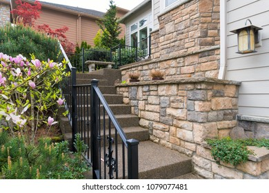 House front entry with concrete stairs iron rod railings stone wall planter siding by frontyard garden