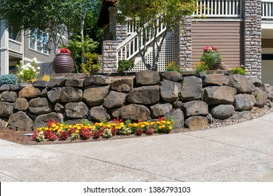 House front yard garden landscaping with cut rocks retaining wall stone works facade with potted plants and flowers