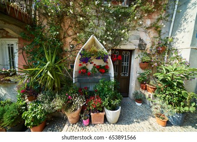 House full of flowers with decorated old boat covered in red flowers