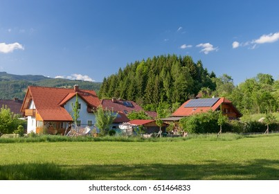 House with garden and solar panels on the roof. View of village and hause with garden and solar panels on the roof.