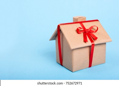 House as a gift on a blue background. A gift wrapped in kraft paper in the form of a house and tied with a red ribbon. Copy space for text