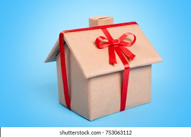 House as a gift on a blue background. A gift wrapped in kraft paper in the form of a house and tied with a red ribbon