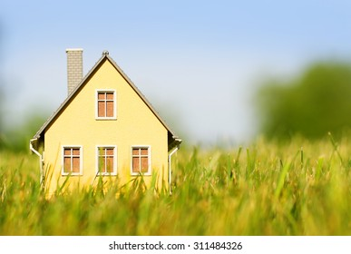 House in green grass over blue sky. Mortgage concept