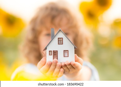 House in hand against spring green background. Real estate concept