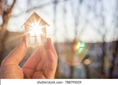 House in hand in the rays of the sun. The concept of protection of property.