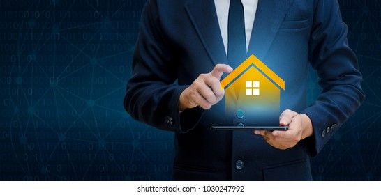 The house is in the hands of the business man  home icon or symbol