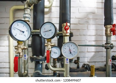 House heating system with many steel pipes, manometers and metal tubes, selective focus