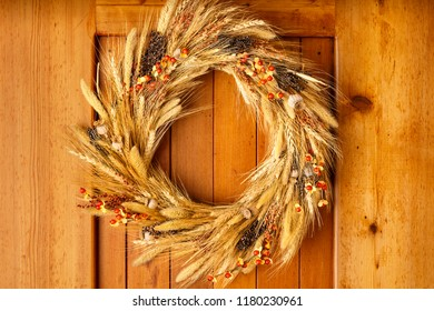 House home front door Fall autumn Thanksgiving decorations country style rustic wreath made of natural botanical materials on wood background