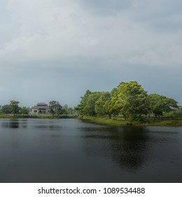 House, home with lake and tree under cloudy sky