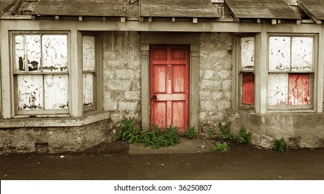 House of Horrors Concept with decayed creepy Entrance with weeds around Red stained Door