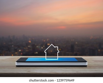 House icon with copy space on modern smart mobile phone screen on wooden table over blur of cityscape on warm light sundown, Businesss real estate online concept