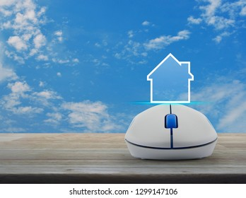 House icon with copy space with wireless computer mouse on wooden over blue sky with white clouds, Business real estate online concept
