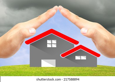 House icon on the green field and blue sky background under 2 open hands attach together like a roof for protection it from the storm.