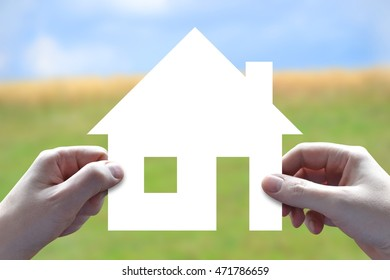 House insurance concept - human hands holding white paper-cut.