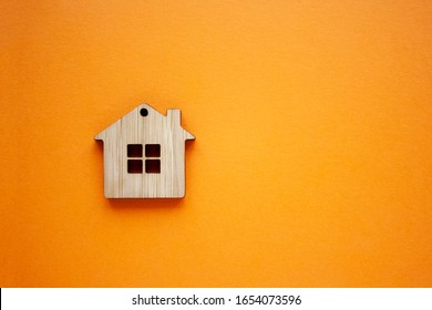House, insurance and mortgage, buing and rent concept. Small wooden house toy on orange background top view copyspace