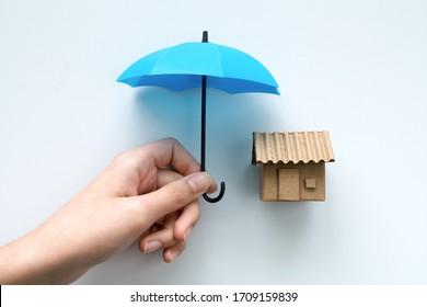Hausversicherung mit einem unter einem blauen Schirm geschützten Haus als Symbol für Wohnsicherheit vor Hypothekenzahlung oder Schäden auf weißem Hintergrund.