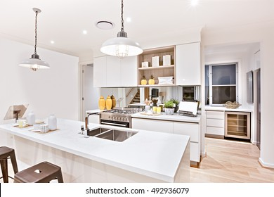 House interior with kitchen decorations including lights and counter close up beside the silver stove and under wooden pantry, the floor is made in wood.
